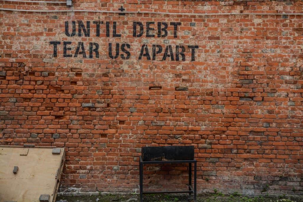 Een muur van bakstenen met een citaat over geld: 'until debt tear us apart'