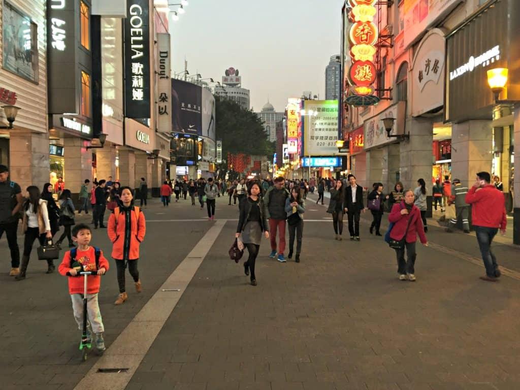 Een winkelstraat met grote ketens en felle lichtgevende reclame aan de gevels