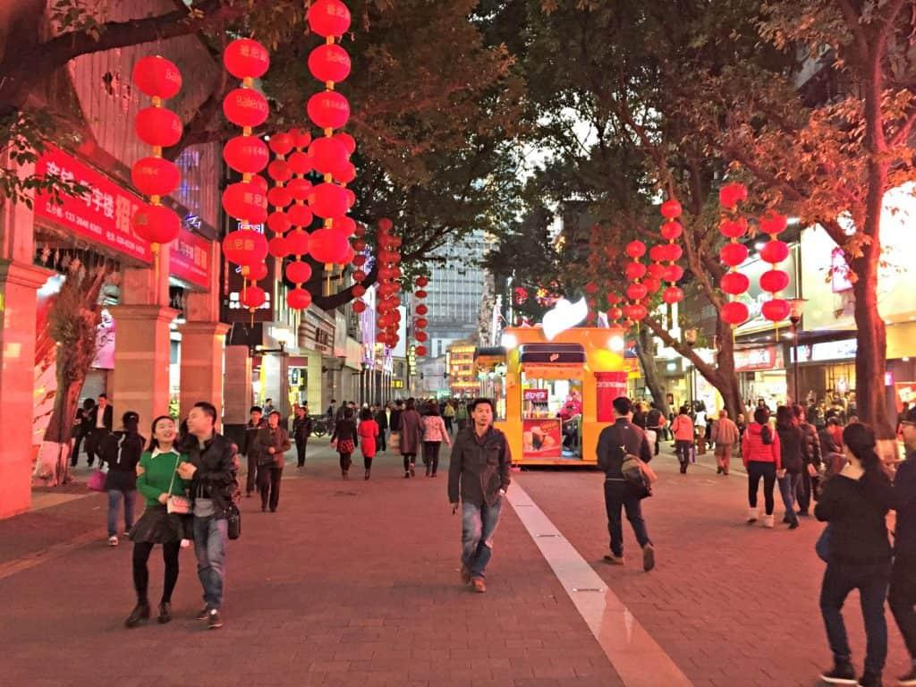 Een winkelstraat met rode lampionnen en Chinese mensen die niet naar ons kijken