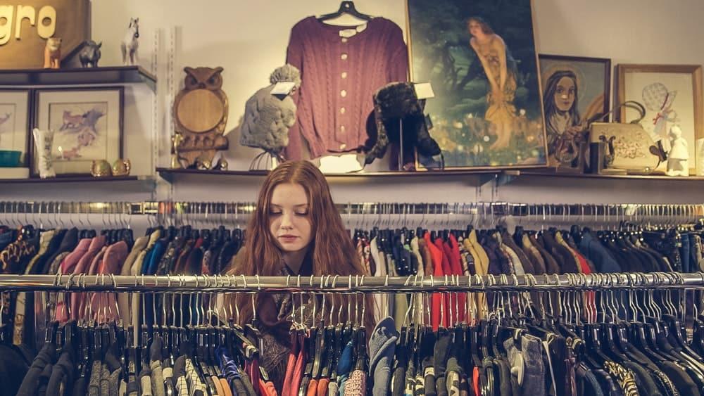 Een vrouw winkelt in een tweedehandskledingwinkel: dat is een beter idee op Black Friday als je nog een studieschuld hebt
