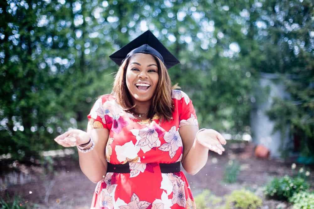 Een vrouw met een square academic cap die met haar handen aangeeft dat ze ook niet weet wat voor studieschuld normaal is