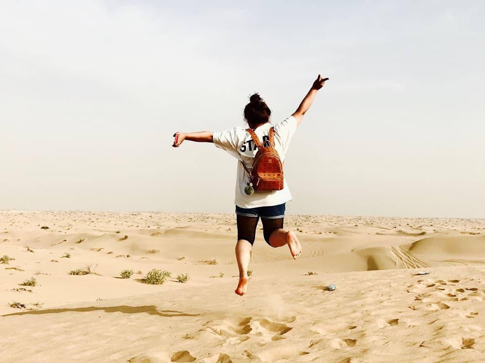 Een vrouw springs gelukzalig omhoog, symbolisch voor hoe gelukkig ik ben sinds ik mijn studieschuld versneld aan het aflossen ben