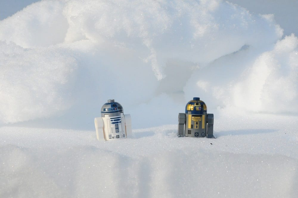 Twee robots van LEGO in de sneeuw: mensen zijn geen robots en dus werkt de sneeuwbalmethode beter bij het aflossen van schulden dan de lawinemethode
