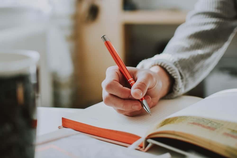 Een arm van een vrouw met een pen en een notitieboek: bij de keuze tussen je studieschuld snel aflossen of niet speelt de rente geen rol