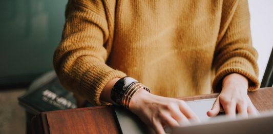 Een vrouw achter een laptop: inloggen bij DUO om je studieschuld te bekijken kan nogal eng zijn