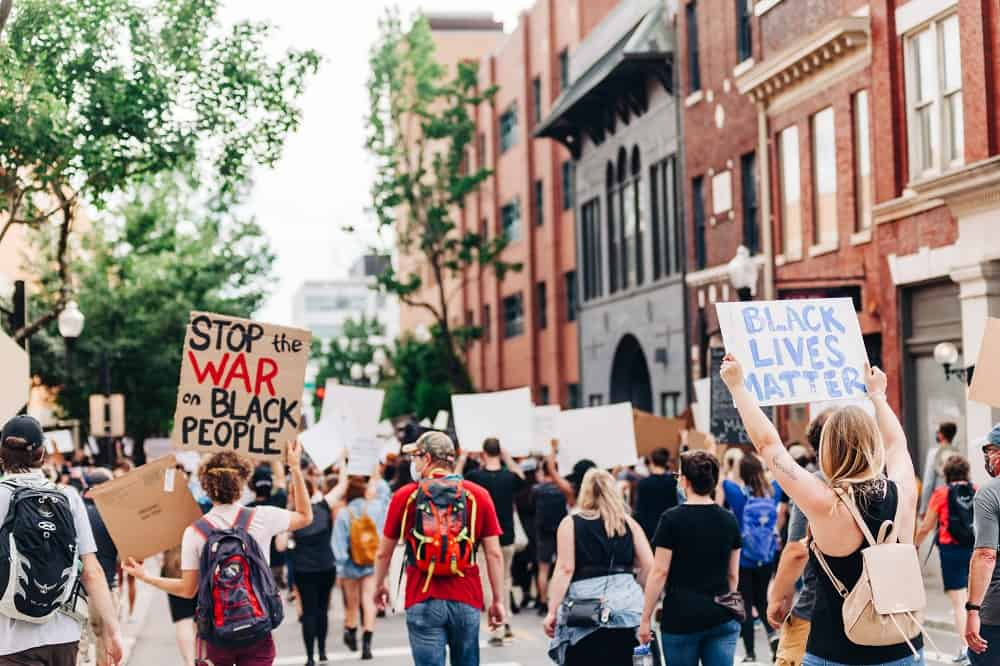 Een protest tegen racisme, een witte vrouw toont een bord met de tekst black lives matter.