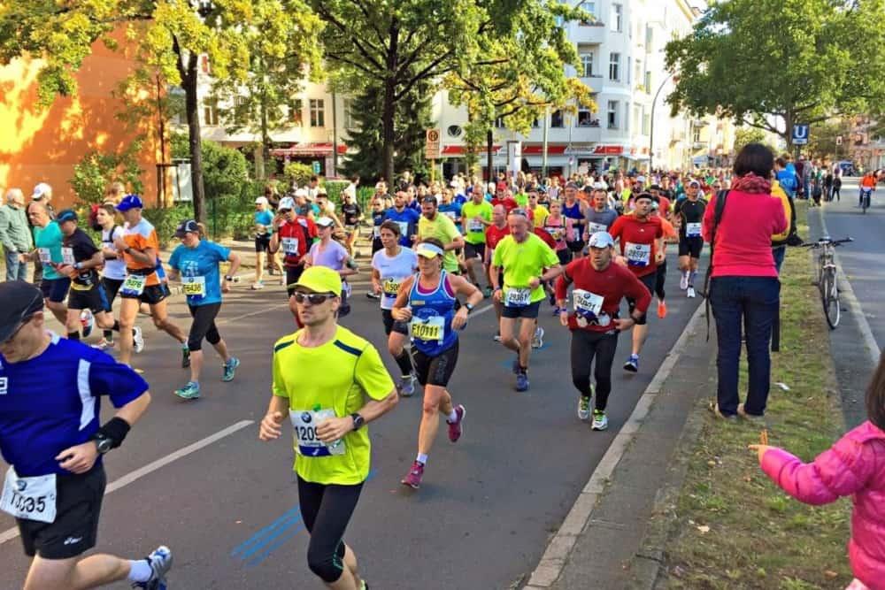 Een lint van gekleurde shirts bij kilometer 22 van de marathon in Berlijn in 2015