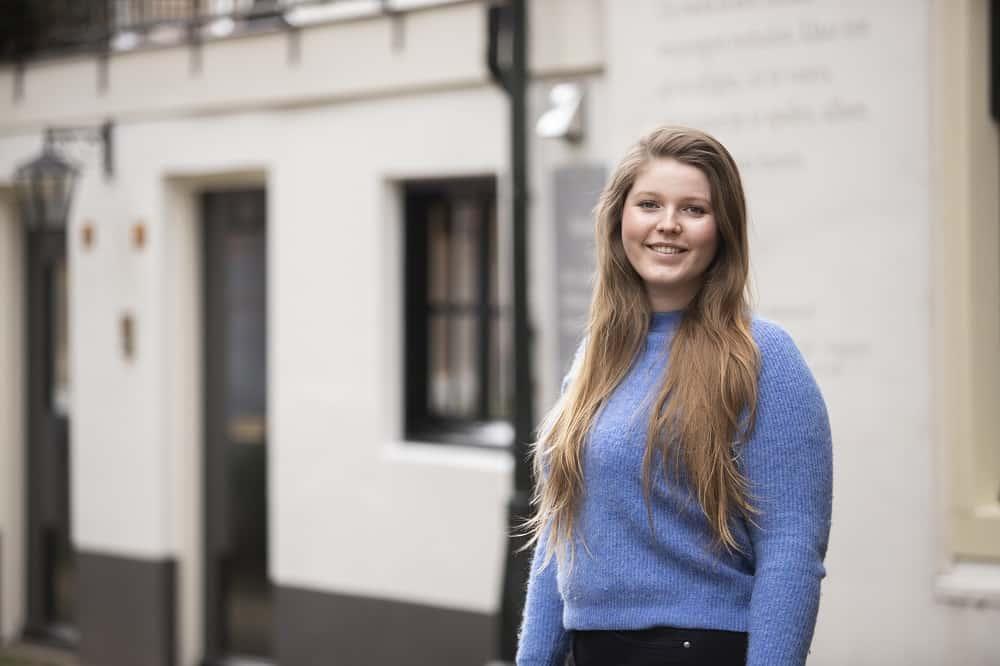 Student Emma Mouthaan lachend in een blauwe trui voor een wit huis, ze vertelt over beleggen en haar studieschuld