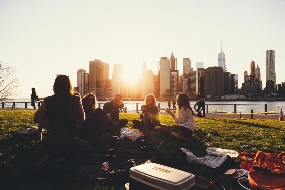 Studenten zitten in het gras te kletsen (misschien geven ze elkaar tips over het laag houden van hun studieschuld)