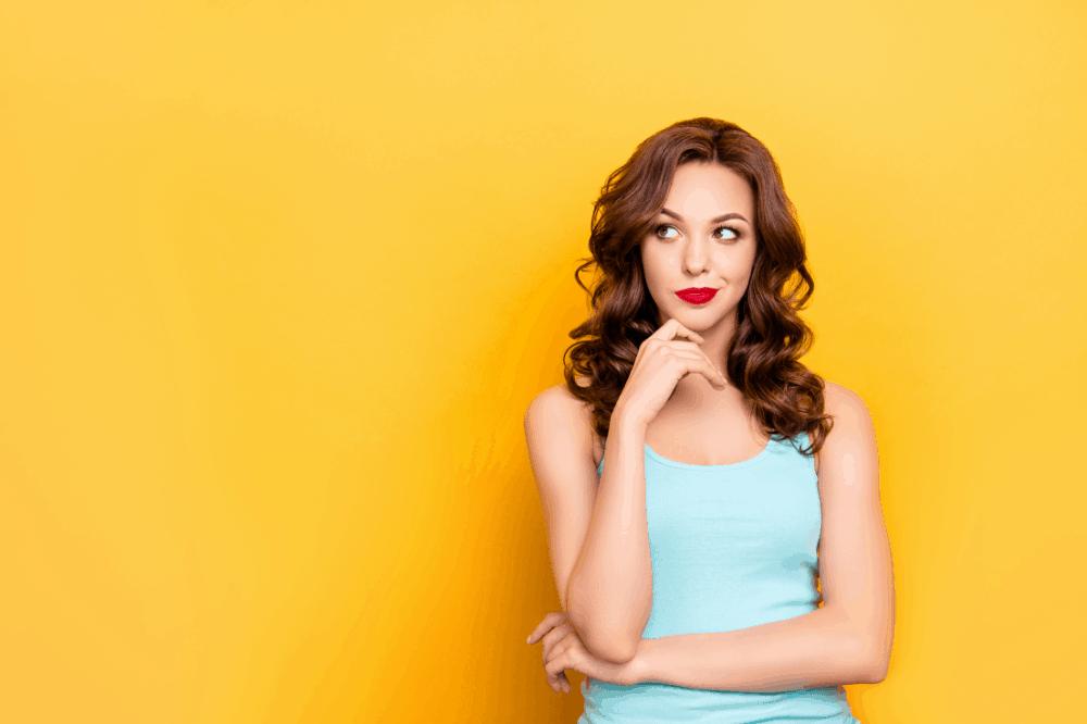 Een witte vrouw met bruine krullen kijkt twijfelachtig opzij, ze staat voor een gele muur, wellicht gaat haar twijfel over deelname aan Zin in Aflossen, de aflostraining van Fuck Die Studieschuld
