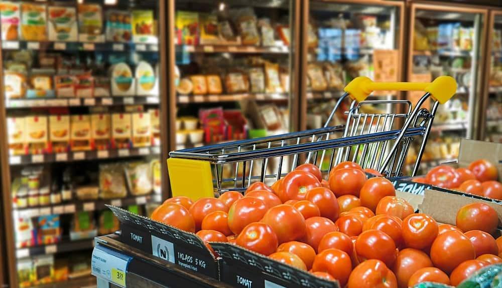 Koelkasten in een supermarkt, met een winkelwagentje ervoor en een grote stapel tomaten (ik kocht veel te veel boodschappen in november en gelukkig zat mijn perfectionisme mij dit keer niet in de weg)