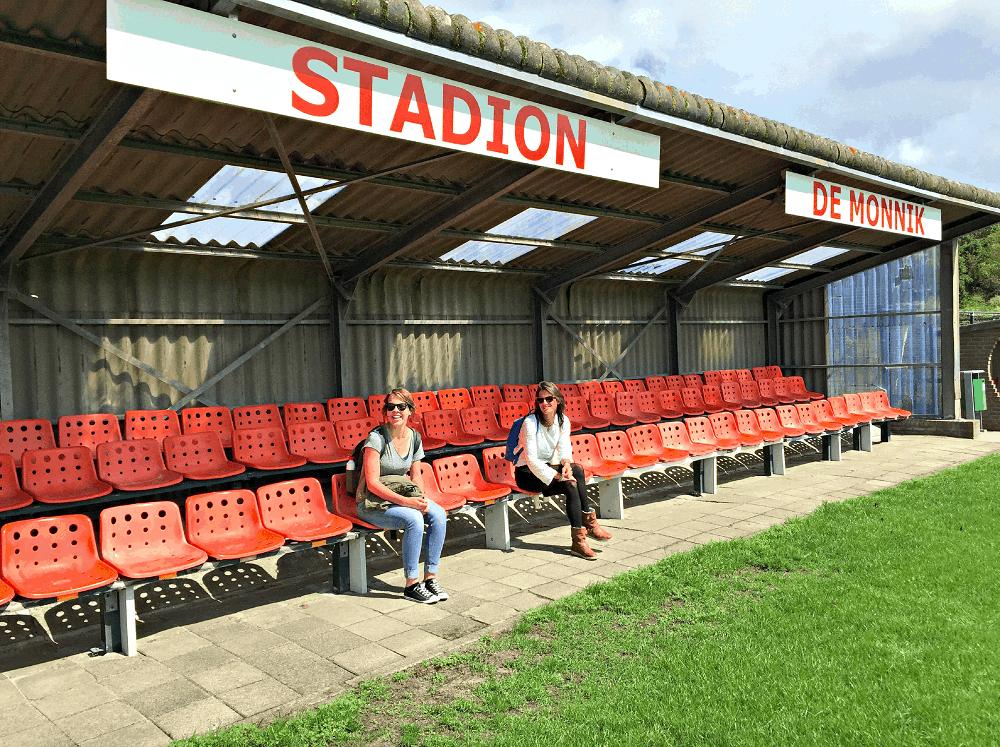 Twee jonge vrouwen zitten in de zon op stoeltjes van voetbalvereniging De Monnik op Schiermonnikoog