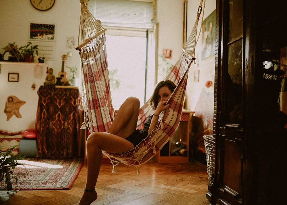 Een vrouwelijke student zit in een hangmat en kijkt wat onzeker in de camera, misschien twijfelt ze of ze nog wel compensatie voor het leenstelsel krijgt als ze haar studieschuld extra snel gaat aflossen
