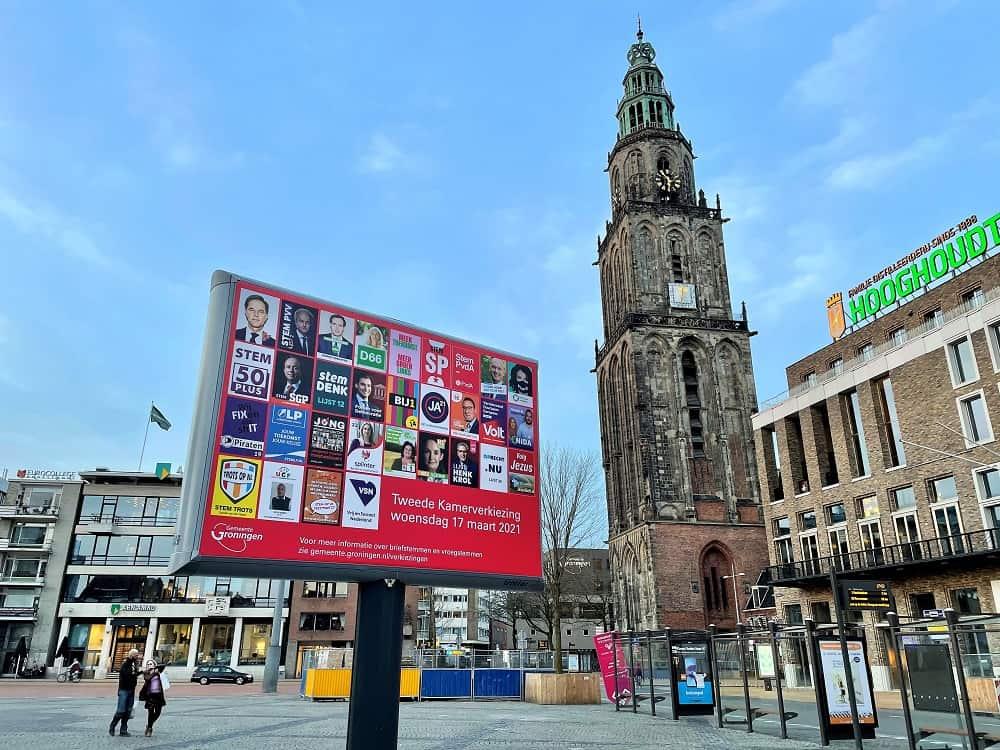 Een bord met verkiezingsposters op de Grote Markt in Groningen, rechts ervan de Martinitoren (in de race naar de verkiezingen van 17 maart zeggen bijna alle partijen het leenstelsel te willen afschaffen, alleen de VVD wil het behouden)