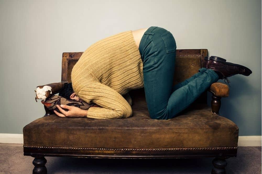 Iemand ligt gehurkt ondersteboven op een stoel, hoofd verstopt in een kussen, wellicht voelt deze persoon schaamte voor een studieschuld