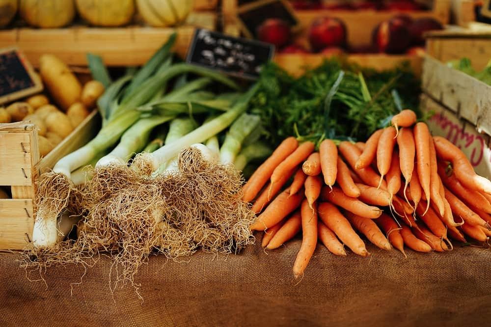 Prei en wortels in een marktkraam (producten kopen op de markt kan je veel geld besparen)
