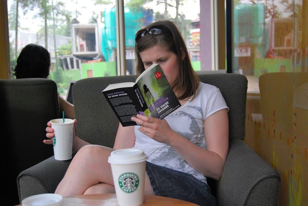 Maaike zit in een Starbucks in Indonesië met een koffie in haar hand (verre reizen en dure koffies, zo zag haar bestaan als twintiger eruit)