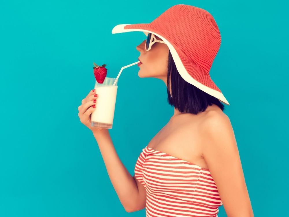 Zijaanzicht van een witte vrouw met zonnebril en hoed, ze drinkt een milkshake (ze is klaar voor de zomer en wellicht ook voor de Zomerserie van Fuck Die Studieschuld)