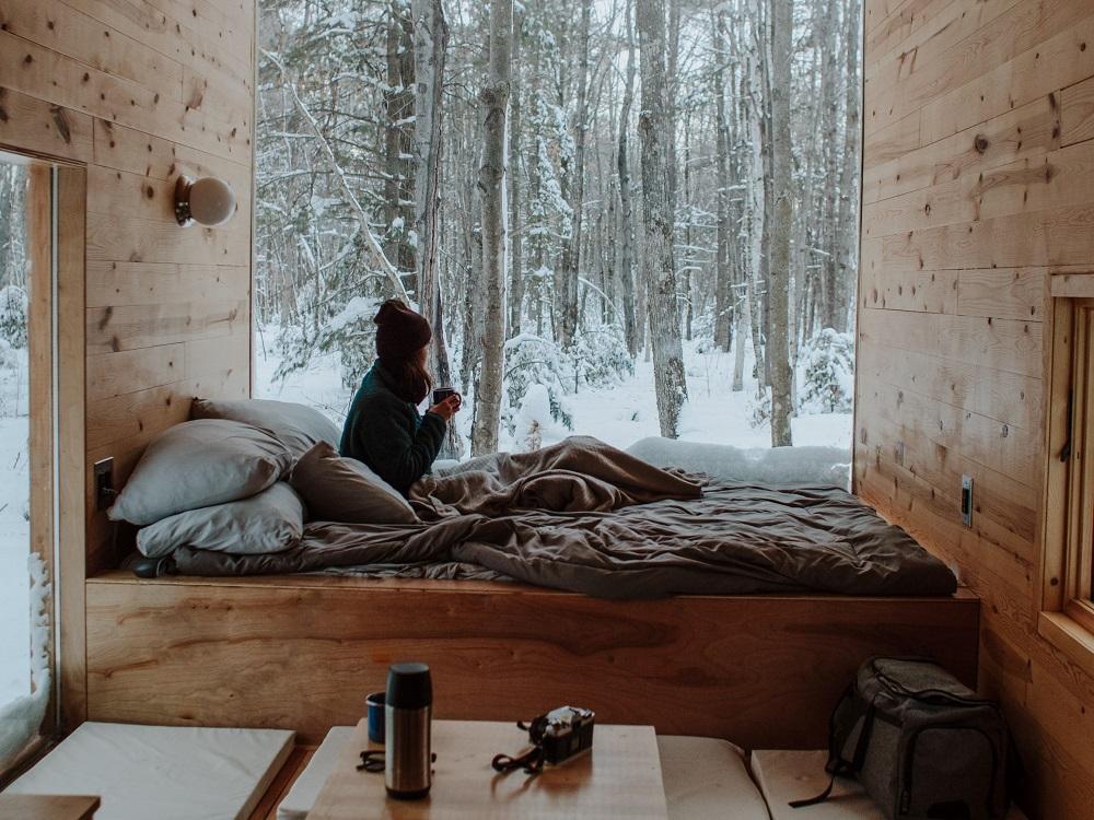 Het interieur van een huisje in het bos, modern, lichte houten balken, een groot raam met uitzicht op bomen, er ligt sneeuw, binnen voor het raam staat een bed, daarop zit een vrouw met een muts en een beker in haar handen, ze kijkt naar buiten