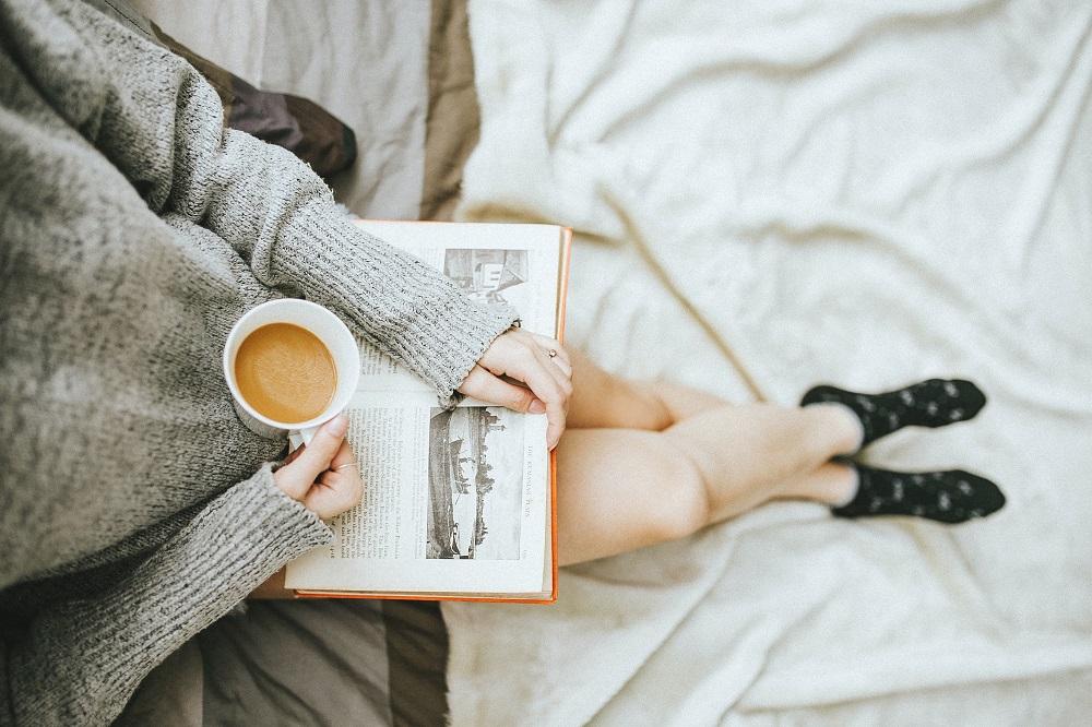 Een witte vrouw zit met gekruiste blote benen, haar hoofd is niet zichtbaar, op haar schoot een boek, in haar rechterhand een kop koffie, ze draagt zwarte sokken en het geheel ziet er comfortabel uit (symbolisch voor hoe self-care niet duur hoeft te zijn)