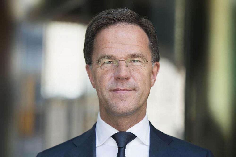 Een portretfoto van Mark Rutte, hij kijkt recht in de camera en glimlacht licht (de vraag is wat hij gaat doen nu de Tweede Kamer het leenstelsel wil afschaffen)