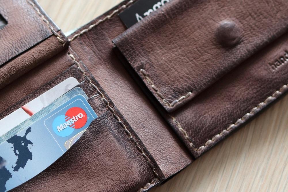 Een bruine portemonnee van leer, aan de linkerkant zitten bankpasjes, rechts een vakje voor muntjes met een knoopje (symbolisch voor de vraag of je YNAB kunt gebruiken zonder creditcard)