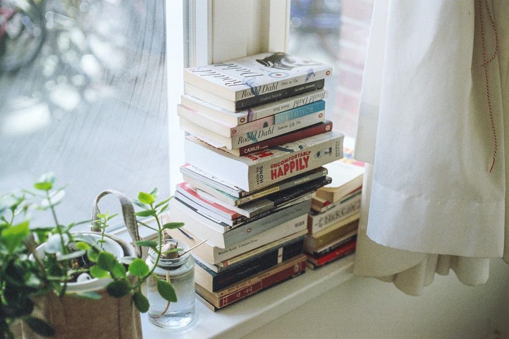 Boeken (hier opgestapeld voor een raam) horen zeker bij de dingen die ik niet meer koop